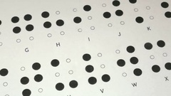Footage of the Braille writing system alphabet, the shot is moving from right Stock Footage