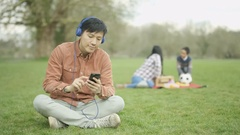 4K Man listening to music in the park with mother & son in background Stock Footage