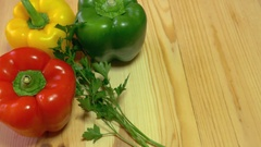 A person decorates a wooden table and puts a red, green and yellow paprika on it Stock Footage