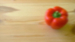 Footage of a red paprika lying on a wooden table, the shot is coming into focus Stock Footage