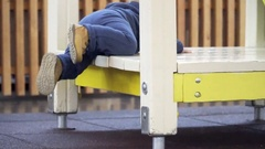 A little boy trying to climb in house on the playground. Legs close-up Stock Footage