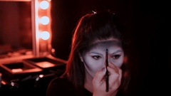 Girl makes a make-up in the style of a witch Halloween Stock Footage