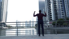 Successful businessman raising arms to the sky, power symbol above city, 240fps Stock Footage