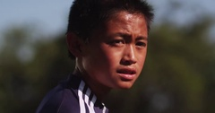 A boy soccer player running down the field with sweat dripping off his face Stock Footage