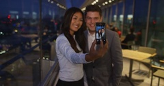 4K Man & woman pose to take selfie with smartphone in city venue at night Stock Footage