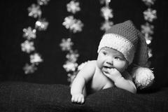Black and white photo of a christmas baby with fingers in mouth Stock Photos