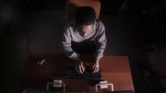 Hacker at night in a dark office hacking computer system Stock Footage