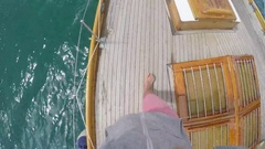 Pov happy man walking on deck of wooden sailboat in ocean on travel adventure Stock Footage
