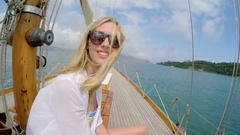 Beautiful woman smiling on sailboat in ocean on luxury lifestyle happy adventure Stock Footage