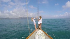 Beautiful girl friends enjoying view arms raised on sailboat in ocean on luxury Stock Footage