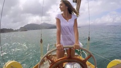 Beautiful woman steering luxury wooden sailboat on adventure travel vacation Stock Footage