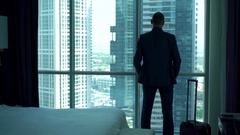 Young businessman enter the hotel room with splendid view and looking through th Stock Footage