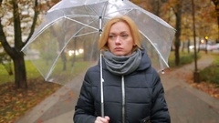 Girl in the rain with an umbrella. autumn woman walking down the street Stock Footage