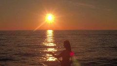 AERIAL: Attractive young woman stand up paddle boarding on sunny summer evening Stock Footage