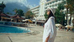Beautiful young woman with long hair walking near the swimming pool. Tourist in Stock Footage