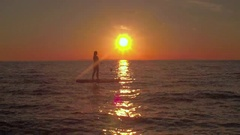 AERIAL: Happy young female rider stand up paddleboarding at dreamy golden sunset Stock Footage