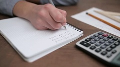 Female accountant making calculations and taking notes Stock Footage
