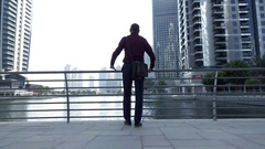 Handsome man looking on the river in the modern city, super slow motion Stock Footage
