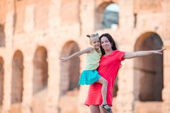 Young mother and little girl exploring Coliseum outside in Rome, Italy. Family Stock Photos