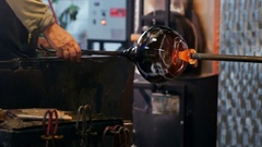 Team of glassblowers shaping a molten glass Stock Footage