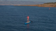 AERIAL: Female rider standup paddleboarding along beautiful sharp rocky shore Stock Footage