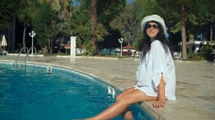 Slender young woman in a hat sits on the edge of the swimming pool, sexy long Stock Footage