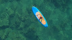 AERIAL: Girl rider standup paddleboarding in beautiful crystal clear emerald sea Stock Footage