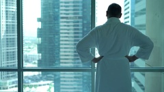 Man in bathrobe admire city view from the window, 4K Stock Footage