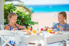 Lunch time. Little girls having breakfast at outdoor cafe with sea view Kuvituskuvat