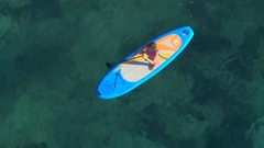 AERIAL: Girl rider standup paddleboarding in beautiful crystal clear blue sea Stock Footage
