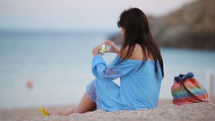 Young woman take a picture on phone on the beach at the evening Stock Footage