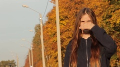 A girl in a hoody with her hair loose standing with her hand up and hitchhiking Stock Footage
