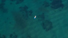 AERIAL: Sporty female rider supping in stunning deep blue Mediterranean ocean Stock Footage