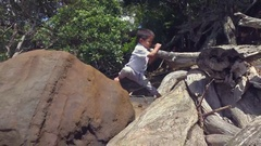 Kid Climbing On a Log at beach. Stock Footage