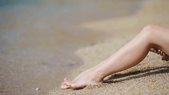 Female slender smooth legs on white sand beach Stock Footage