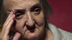 Lonely elderly woman at home: depressed old woman sitting alone  Stock Footage