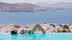 Beautiful young girl relaxing on the edge of swimming pool outdoors with Stock Footage
