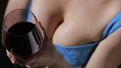 Woman with big breasts holding a glass of red wine. close-up Arkistovideo