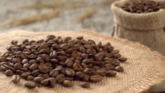 Close-up of roasted coffee beans rotating on burlap. Rustic wooden background Stock Footage
