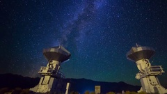 Astro Timelapse of Galaxy over Symmetric Radio Observatories -Pan Right- Stock Footage