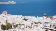 Beautiful young woman reading book in luxury hotel with amazing view on Mykonos Stock Footage