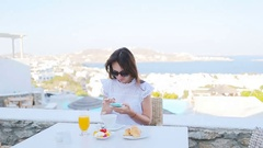 Beautiful elegant lady having breakfast at outdoor cafe with amazing view on Stock Footage