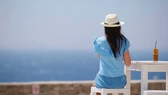 Young girl drinking cold coffee enjoying sea view. Beautiful woman relax during Stock Footage