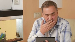 Aged man with a mustache in coughs and communicate with a doctor on a video Stock Footage