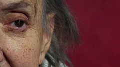 Half face portrait of an old wrinkled woman sitting lonely at home  Stock Footage