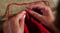 Grandmother knits a sweater sitting in front of a fireplace Stock Footage