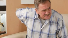 Senior man with a mustache could not get off the couch because of back pain. He Stock Footage