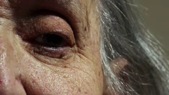 Old woman's eye closeup portrait: wrinkled old woman's portrait  Stock Footage