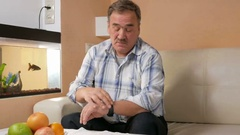 Senior man mustache checks messages on the smart watch at home. He sits on the Stock Footage