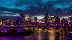 Zoom night time panorama of Brisbane city with purple lights on Story Bridge Stock Footage